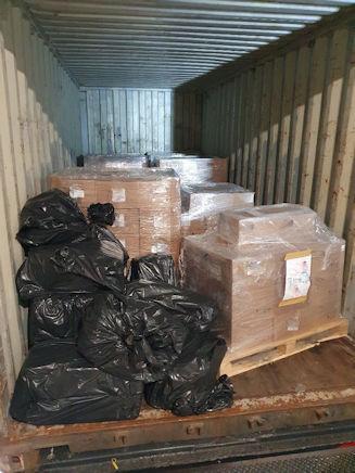 Schwarze Plastiksäcke neben Kartons