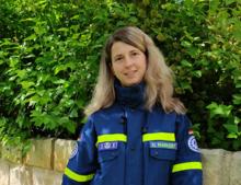 Junge Frau in blauer Einsatzkleidung des technischen Hilfswerks vor einer grünen Hecke.