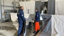 Zwei THW-Helfer reinigen THW-Zelte in Hilden und tragen dabei blaue Regenkleidung