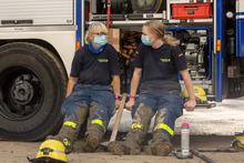 Zwei Helferinnen sitzen auf der Stufe eines Gerätekraftwagens. Beide tragen blaue THW-Einsatzkleidung, die mit Schlamm verschmiert sind.