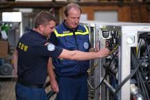 Zwei Männer in Einsatzkleidung betrachten ein Gerät. Der rechte der Beiden ist THW-Präsident Gerd Friedsam.