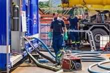 Mann in blauer Einsatzkleidung des Technischen Hilfswerks mit Atemschutzmaske im Gesicht und Arbeitshandschuhen. Links von ihm steht ein Einsatzfahrzeug, an dem Schläuche befestigt sind. Im Hintergrund befindet sich eine Separationsanlage.