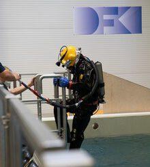 Ein Mensch in schwarzem Taucheranzug und gelbem Taucherhelm steigt in ein Wasserbecken. An der Wand dahinter ist das Logo des Deutschen Forschungszentrums für Künstliche Intelligenz (DFKI) zu sehen.