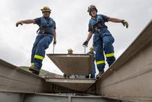 Das Bild zeigt zwei Helfer beim Aufbau der Brücke.